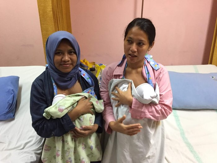 Two mothers holding infants