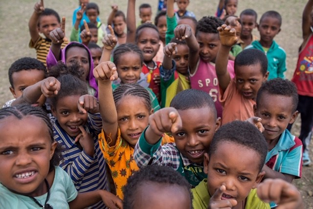 Crowd of young students in Ethiopia pointing at the camera excitedly