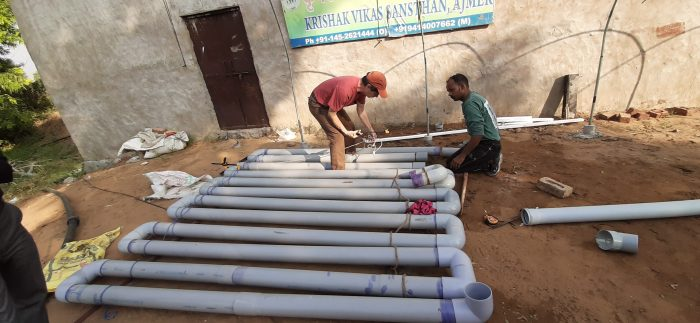 Two men working on large pvc pipes in a dirt yard