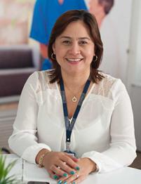 Headshot of Dedsy Berbesi-Fernandez smiling in a white shirt and lanyard